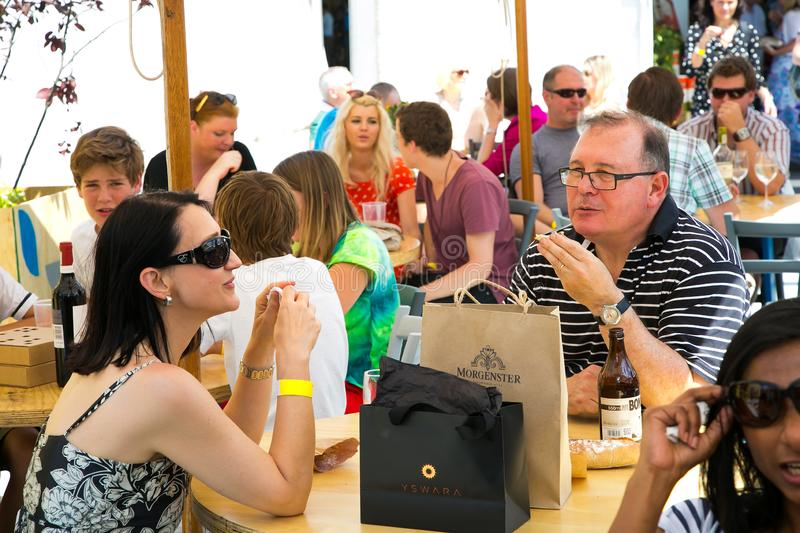 Middle aged couple eating, drinking and generally enjoying a day out at a Food and Wine Fair. Johannesburg, South Africa - November 9 2013: Middle aged couple stock photos