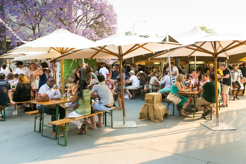Diverse Friends eating, drinking and generally enjoying a day out at a Food and Wine Fair. Johannesburg, South Africa - October 10 2015: Diverse Friends eating stock photos