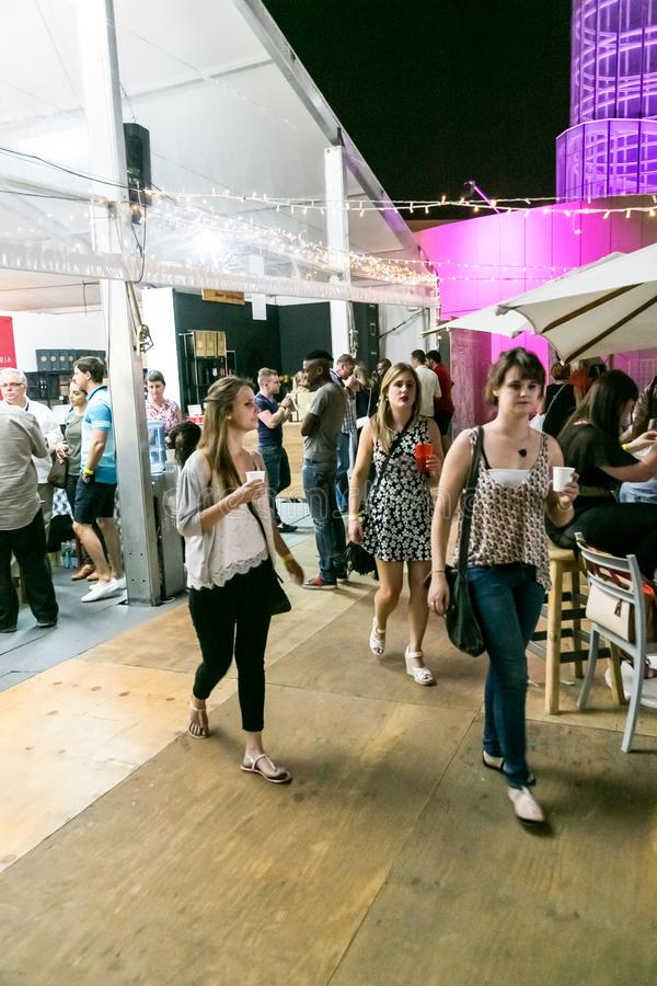 Diverse Friends eating, drinking and generally enjoying a day out at a Food and Wine Fair. Johannesburg, South Africa - October 10 2015: Diverse Friends eating stock image