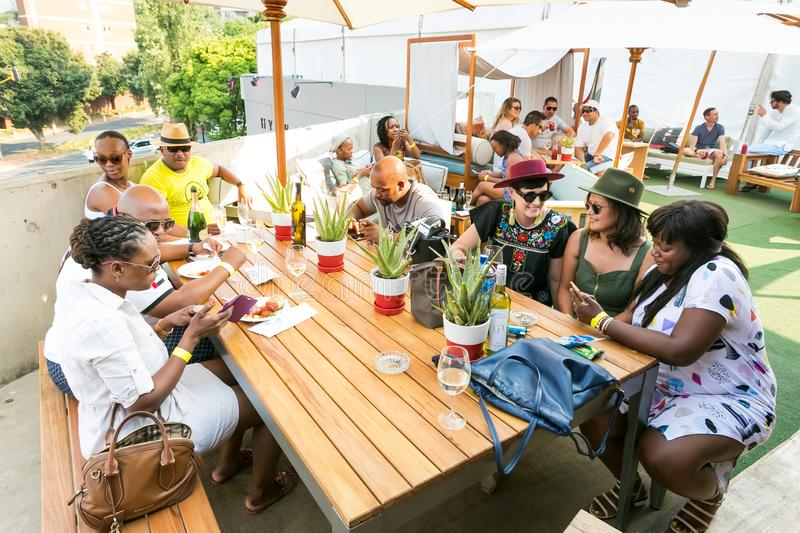 Diverse Friends eating, drinking and generally enjoying a day out at a Food and Wine Fair. Johannesburg, South Africa - October 10 2015: Diverse Friends eating stock images
