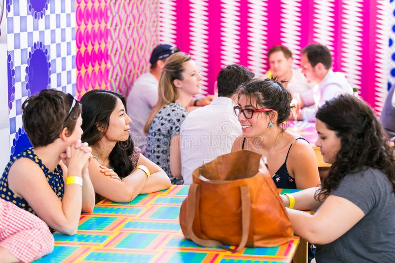 Diverse Friends eating, drinking and generally enjoying a day out at a Food and Wine Fair. Johannesburg, South Africa - October 15 2016: Diverse Friends eating stock photo