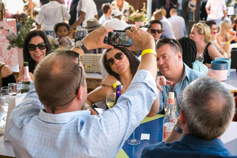 Friends taking a selfie on their phone and generally enjoying a day out at a Food and Wine Fair. Johannesburg, South Africa - October 10 2015: Friends taking a royalty free stock photos