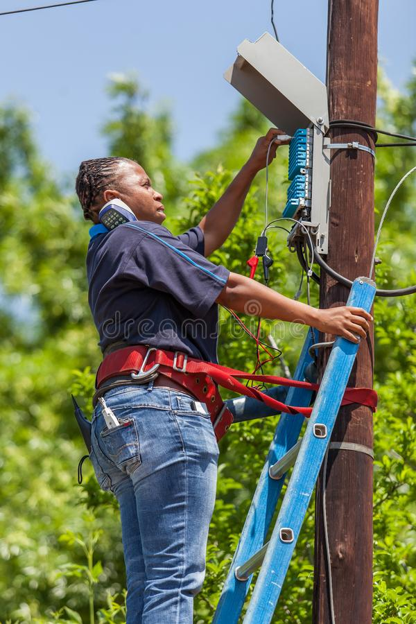 Telephone engineer working on telephone poll. royalty free stock photography