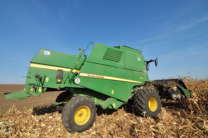 John Deere Big Combine Harvesting The Corn Field In Daytime Against Blue Sky Background