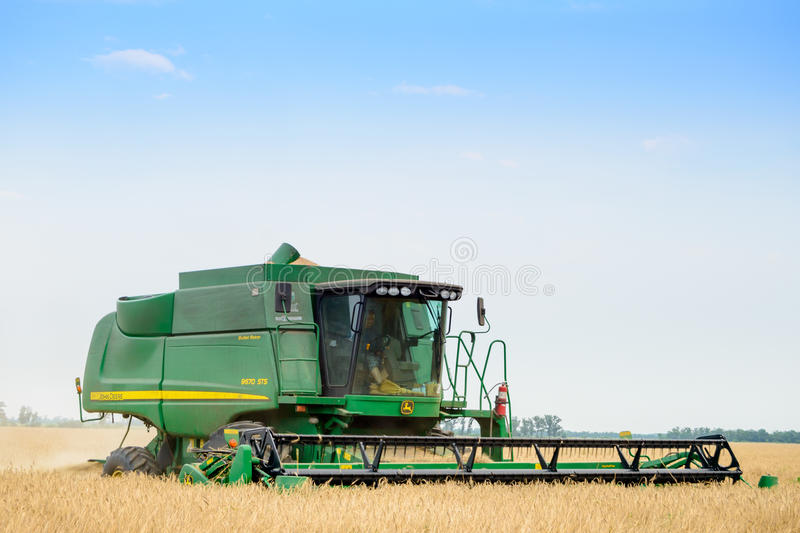 John Deere Combine Harvester Harvesting Wheat in the Field. royalty free stock photo
