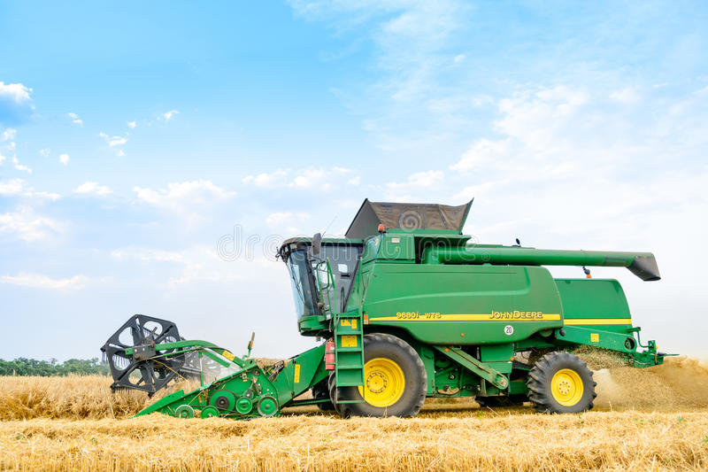 John Deere Combine Harvester Harvesting Wheat in the Field. royalty free stock image