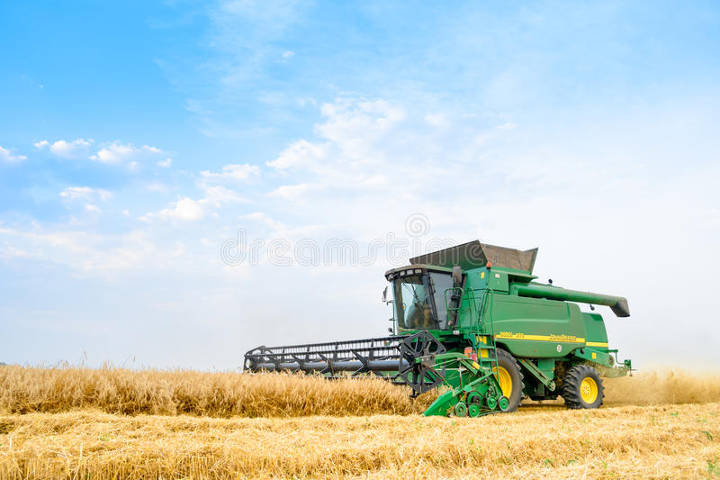 John Deere Combine Harvester Harvesting Wheat in the Field. stock image