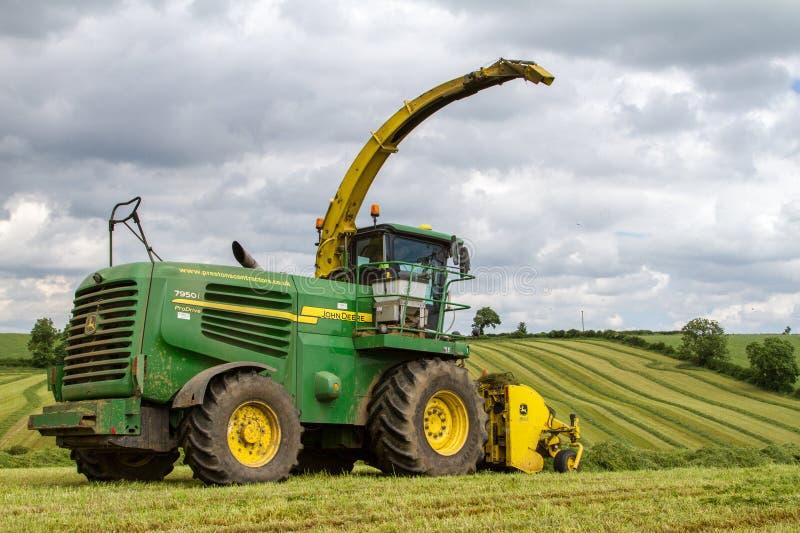 John Deere Forage Harvester met rijen van gras stock afbeelding