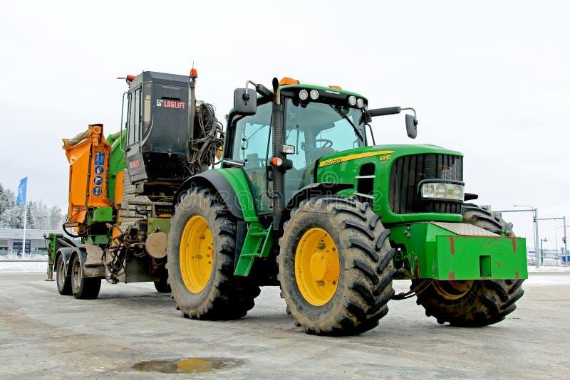 John Deere 6930 jordbruks- traktor med den Wood gå i flisor maskinen arkivfoton