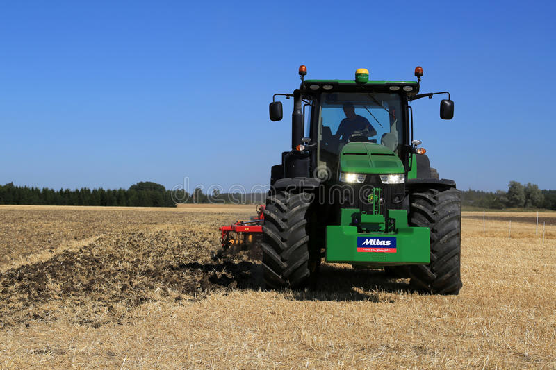 John Deere 8370R Tractor on Field with Headlights on stock images