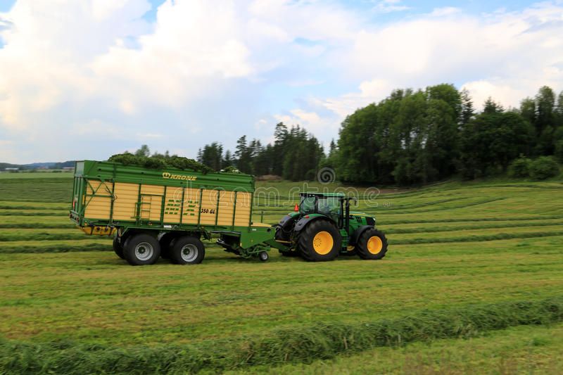 John Deere 6210R Tractor and Full Krone MX 350 GL Forage and Dis royalty free stock image