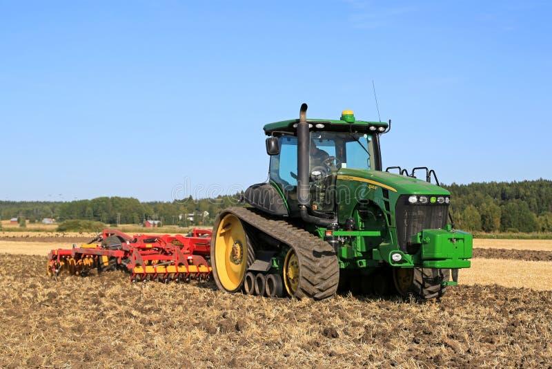 John Deere 8345RT siguió el tractor y al cultivador de Vaderstad en el Fi foto de archivo