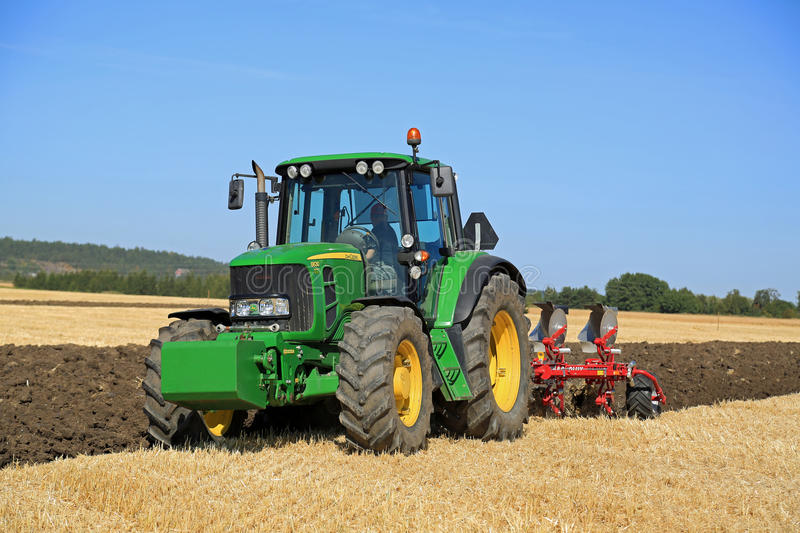 John Deere 6630 Tractor and Agrolux Plow on Field stock photos