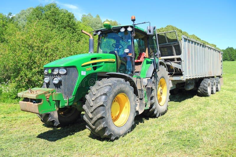 The John Deere 7930 tractor with the dumping Fliegl Gigant ASW 393 semi-trailer. KALININGRAD REGION, RUSSIA - JUNE 11, 2015: The John Deere 7930 tractor with the stock image