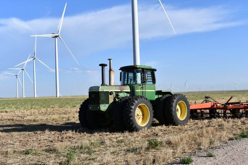 John Deere Tractor z Texas Windmills przeciwko Blue Sky z White Clouds fotografia royalty free