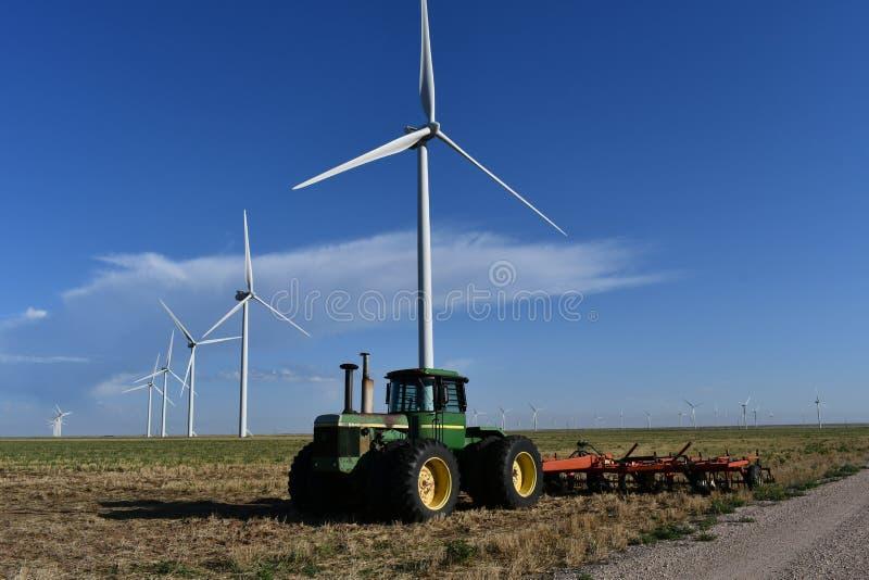 John Deere Tractor z Texas Windmills przeciwko Blue Sky z White Clouds obraz stock