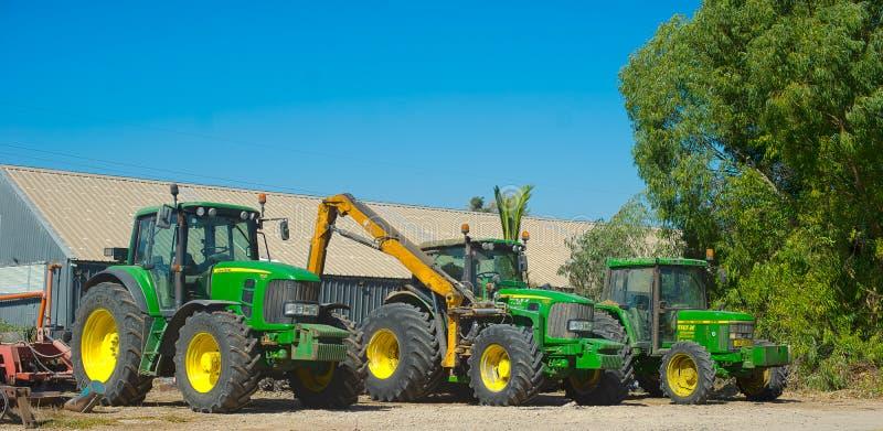 John Deere tractors. Three green John Deere tractors ready to go to work in the fields stock photos