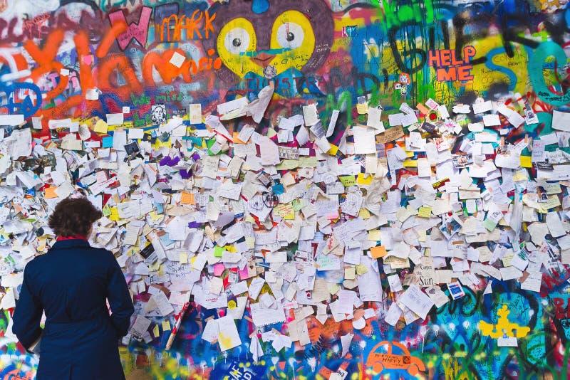 John Lennon Graffiti Wall on Kampa Island in Prague. PRAGUE, CZECH REPUBLIC - SEPTEMBER 11, 2014: Woman looking at Famous John Lennon Wall on Kampa Island in royalty free stock image