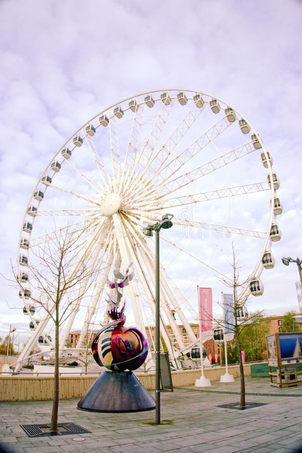 John Lennon Peace Monument and Big Wheel. John Lennon peace and harmony memorial situated on the waterfront near Albert dock and close to the big wheel and the stock image