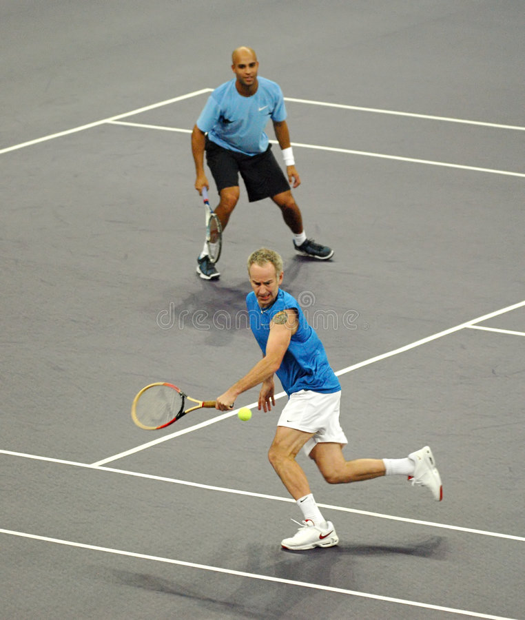 John McEnroe and James Blake in actions. Tennis players John McEnroe and James Blake of the U.S actions during an exhibition tennis match against Roger Federer stock photography