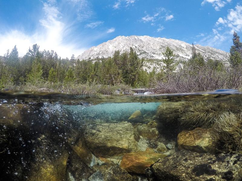 John Muir Wilderness trail in the Eastern Sierra Nevada Mountains in California. Heart Lake, with a split underwater / above water. View stock photography