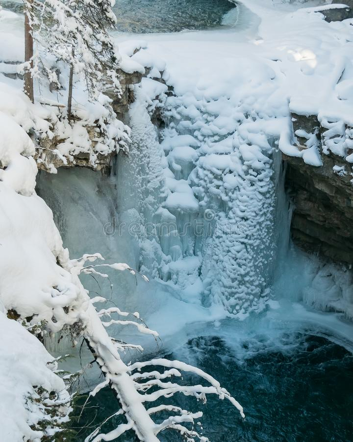 A wintery landscape of snow covered trees and frozen wateralls. Johnston Canyon in Banff National Park, Alberta, Canada, is a year-round destination for visitors stock photos