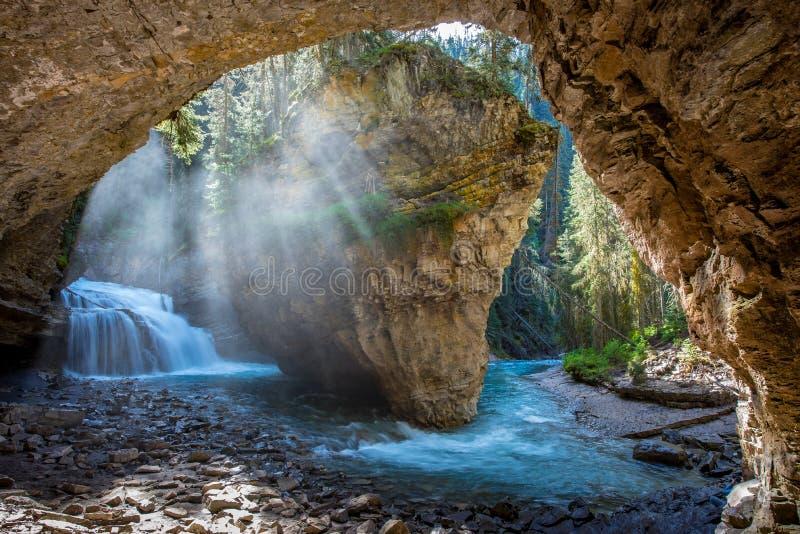 Johnston Canyon grotta i vårsäsongen med vattenfall, Johnston Canyon Trail, Alberta, Kanada arkivfoto