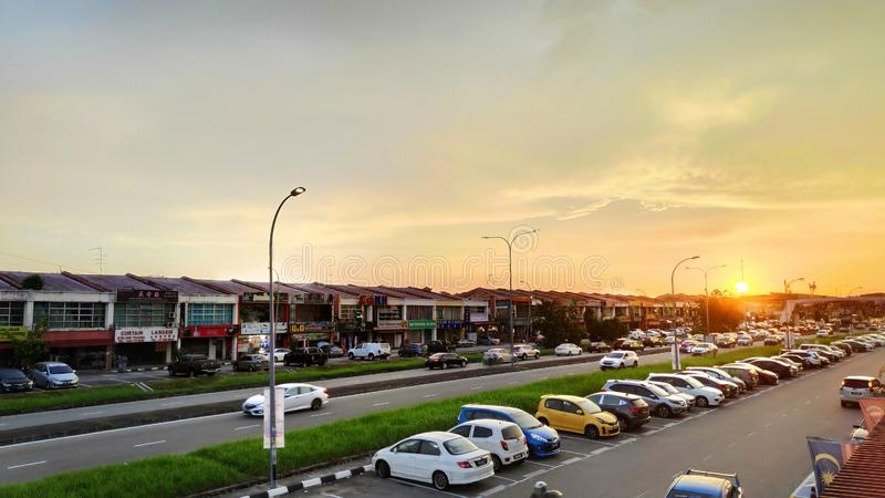 Sunset over ordinary shop houses and car over Johor Bahru in Malaysia. JOHOR BAHRU, MALAYSIA- 25 MAY, 2019: Sunset over ordinary shop houses and car over Johor royalty free stock image