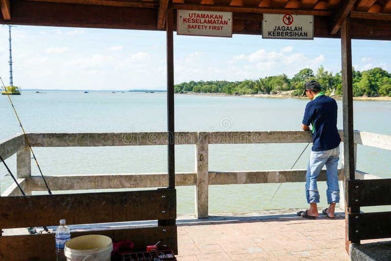JOHOR, MALEISIË - FEBRUARI 2019: Een mens die door de pier in Johor-rivier vissen stock foto's