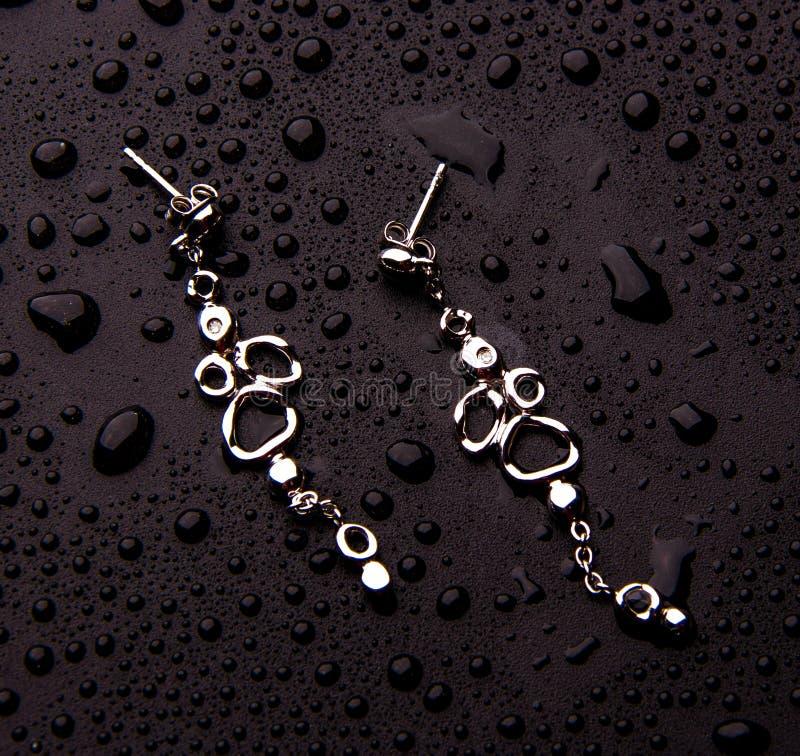 Joia de prata à moda com gotas da água isolada em um fundo violeta fotos de stock