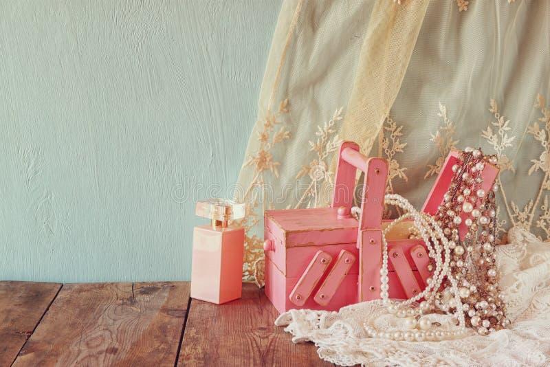 Joia do vintage, caixa de joia de madeira antiga e garrafa de perfume na tabela de madeira Imagem filtrada imagem de stock royalty free