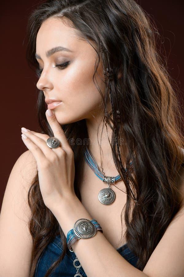 Joia e conceito da forma Um modelo com brincos colar e anel no fundo marrom fotos de stock royalty free