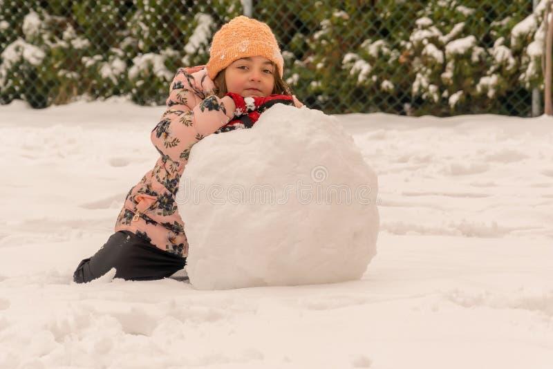 Joie et amusement d'hiver Fille et une grande boule de neige photos stock