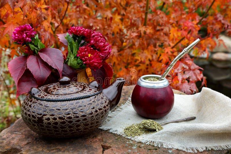 Joignez le thé dans une calebasse sur une table en pierre dans le jardin image libre de droits