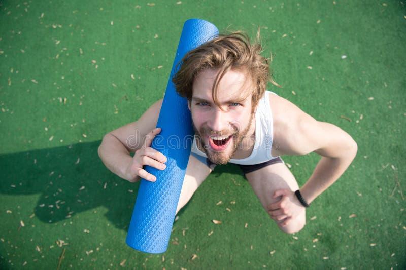 Joignez le yoga Le visage de sourire gai d'athlète d'homme porte le tapis, allant à l'étirage Le sportif porte le tapis de yoga p photographie stock