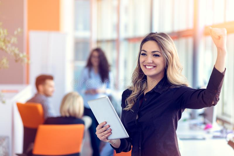 Join a digital age. Cheerful young woman holding digital tablet while his friends working on background stock photo