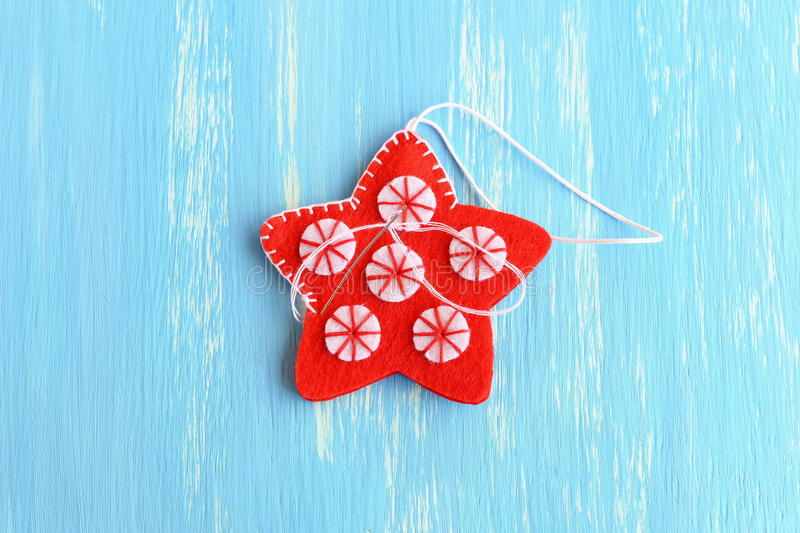 Join the felt edges of Christmas star with white thread using a decorative blanket stitch royalty free stock photography
