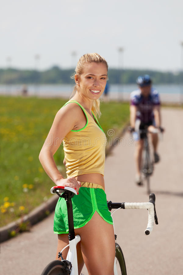 Join me. Girl inviting for bicycle ride stock photography