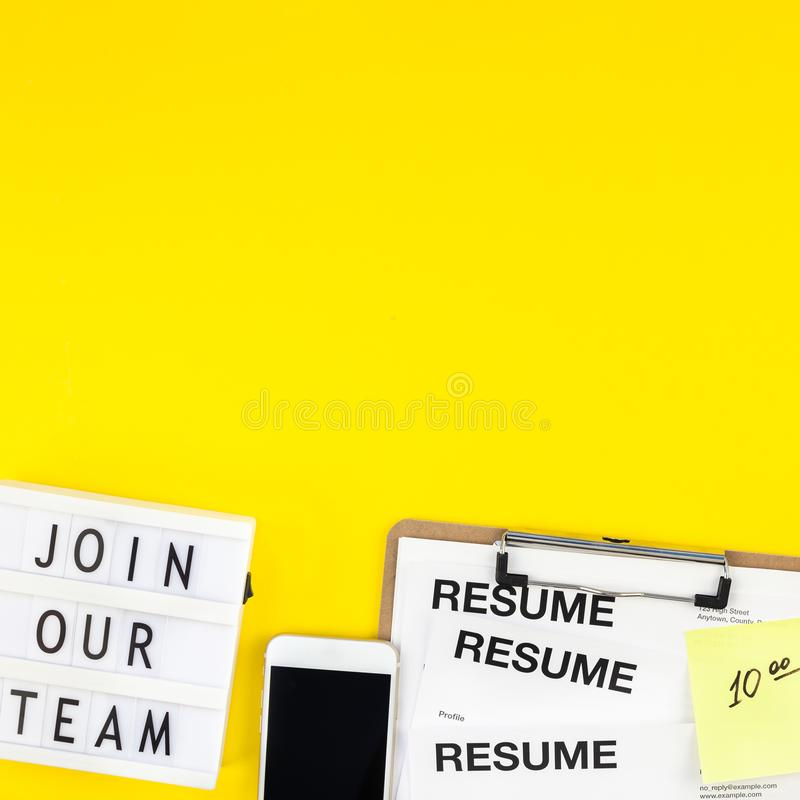 Join our team flat lay on yellow background. Creative top view flat lay of desk with join our team text on lightbox copy space on bold yellow background in royalty free stock photography