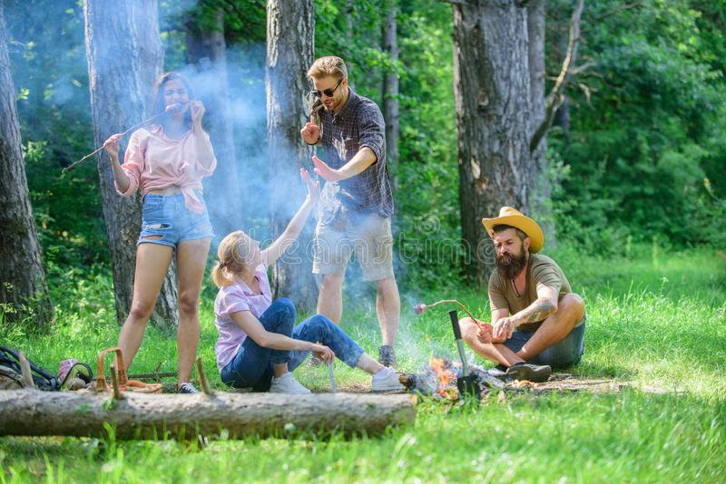 Join summer picnic. Friends meeting near bonfire to hang out and prepare roasted sausages snacks nature background. Gathering for great picnic. Company having stock photo