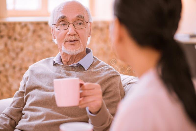 Attentive mature man looking at his nurse royalty free stock photography