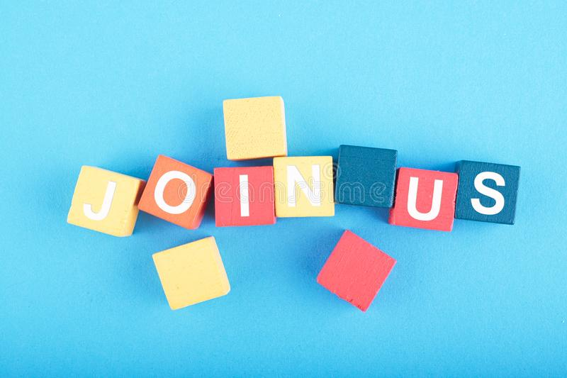 JOIN US word on wooden cube over blue background royalty free stock images