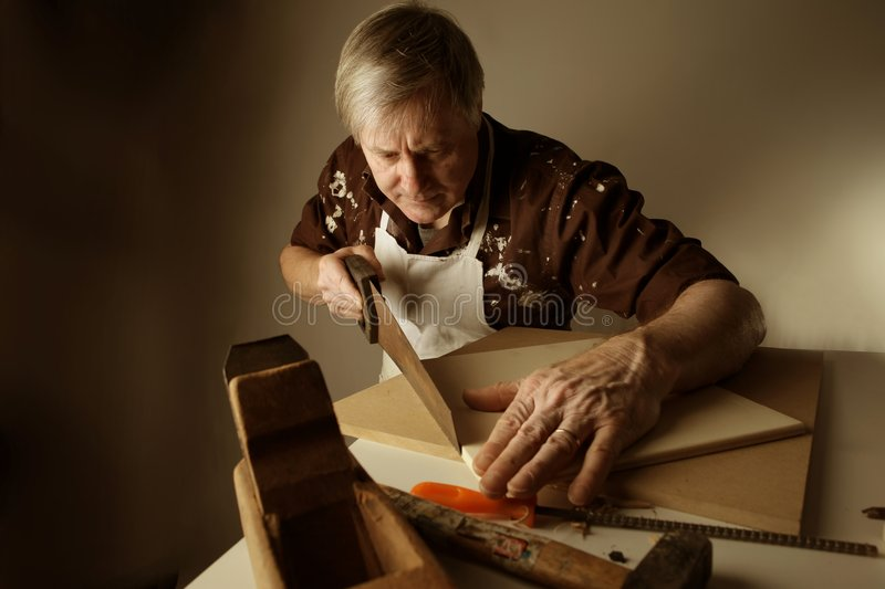 Joiner. A joiner sawing a plank with an handsaw stock images