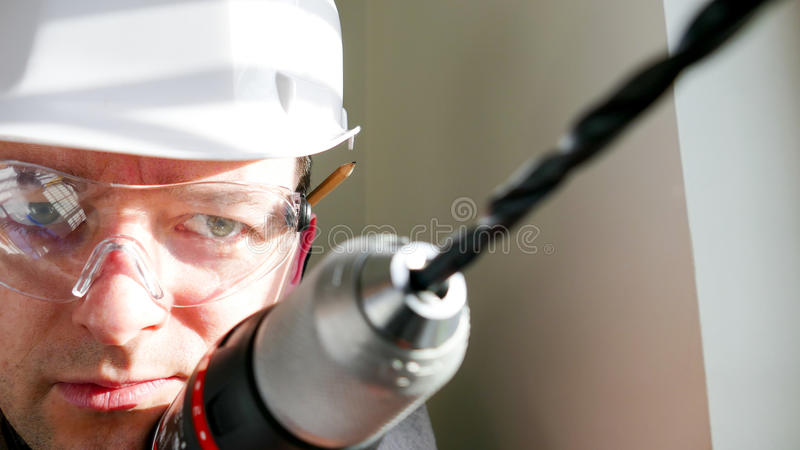 Joiner - handyman drilling in the wall stock image