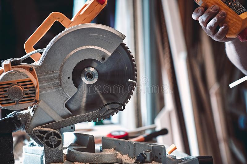 The joiner processes the billet on a circular saw. stock photo