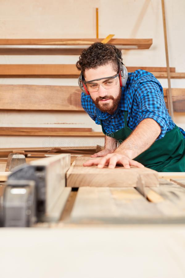 Joiner sawing the wood on the circular saw stock photos