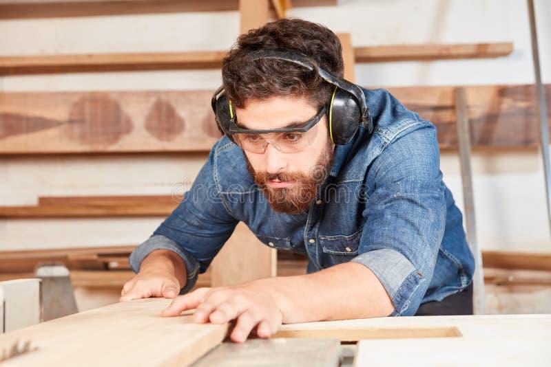 Joiner w warsztacie piłuje drewno fotografia stock