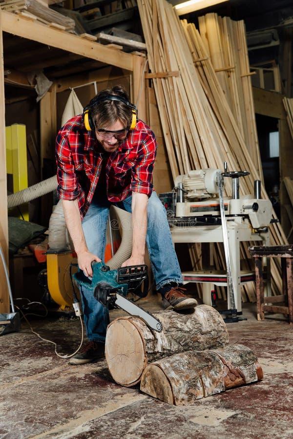 Joiner w warsztacie piłuje drzewa z elektryczną piłą łańcuchową cieśla w trakcie piłowania zdjęcie stock