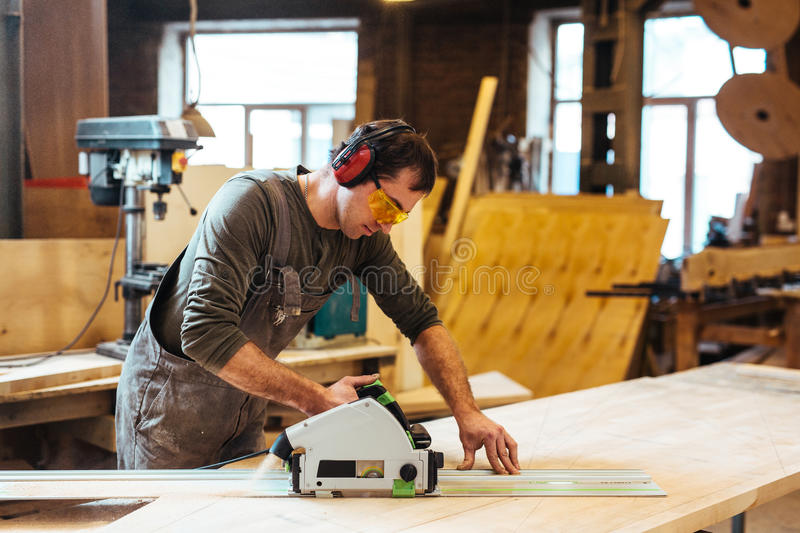 Joiner at work. Modern joiner working with electric fretsaw in workshop royalty free stock image