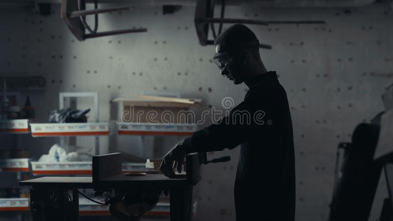 Joiner works with an electric jigsaw and processes wooden products. royalty free stock image